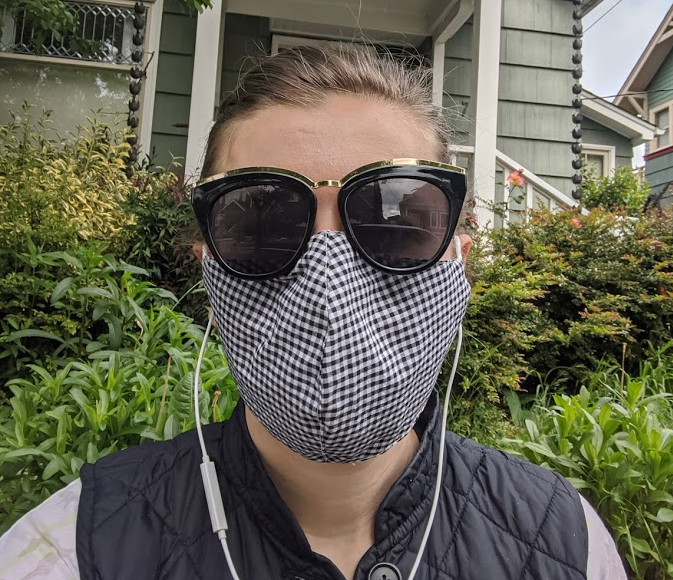 The author standing outside wearing a cloth face covering and dark sunglasses.