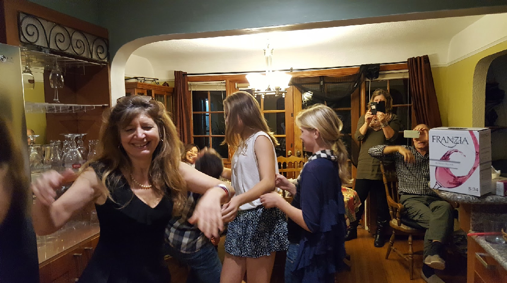 Family dancing in a kitchen, happily. There is box wine on the counter.