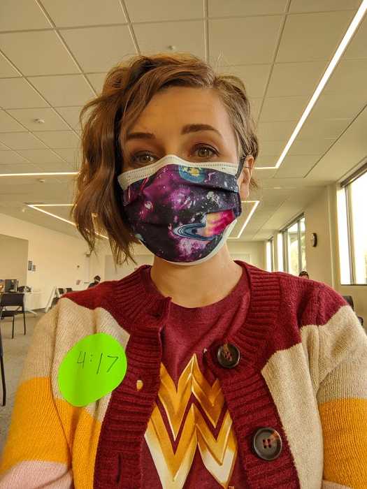 Woman wearing a surgical mask, sitting inside a large waiting room.